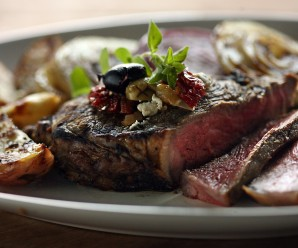 A marinade will add flavor and it will help tenderize the meat when making this grilled strip steak garnished with olives and feta cheese. (Kimberly P. Mitchell/Detroit Free Press/MCT)