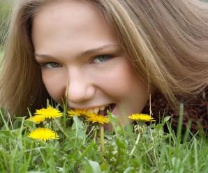 pretty girl fooling around (biting dandelionm)
